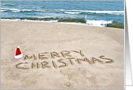 Merry Christmas written in beach sand with Santa hat card